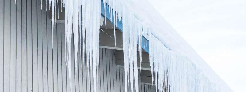 Zdjęcie śniegu i sopli zwisających z dachu hali